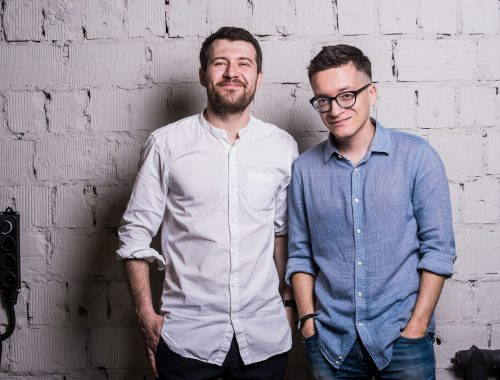 Two young men startupers over grey brick wall loft | Web development Las Vegas